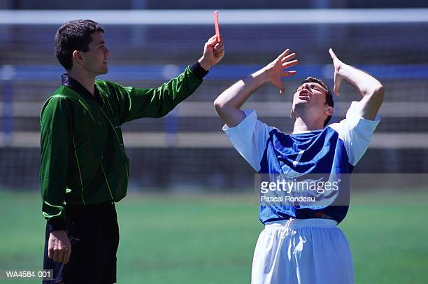 Soccer referee holding red penalty card at soccer player