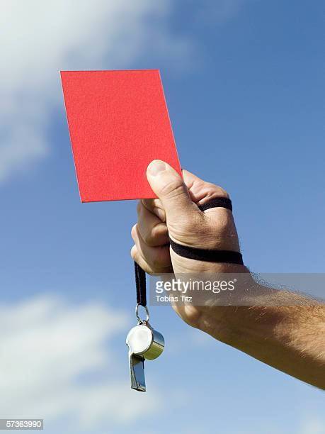 A soccer referee holding up a red card
