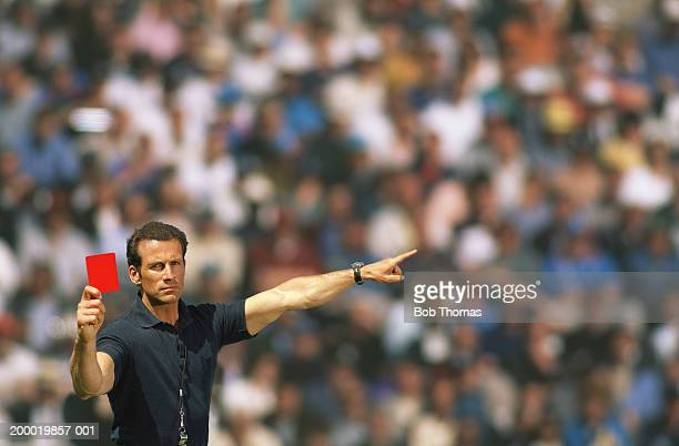 Soccer referee holding up red card, portrait (Digital Composite)