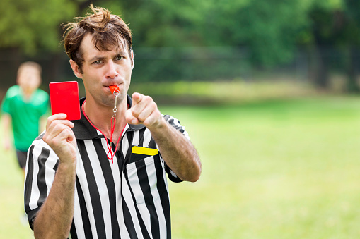 Soccer referee points and holds up red card 613216544