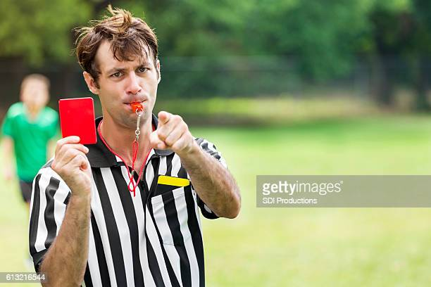 Soccer referee points and holds up red card