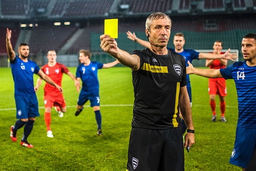 Soccer referee showing yellow card 901265136