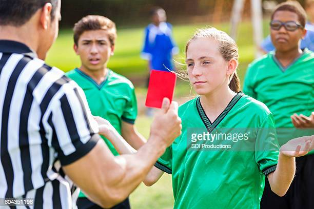 Soccer referee shows red card to female soccer player
