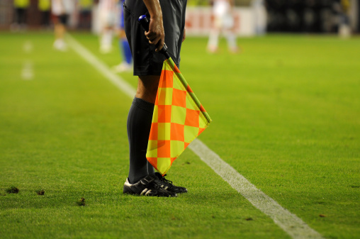 Soccer referee's checkered flag on a soccer field 156620564