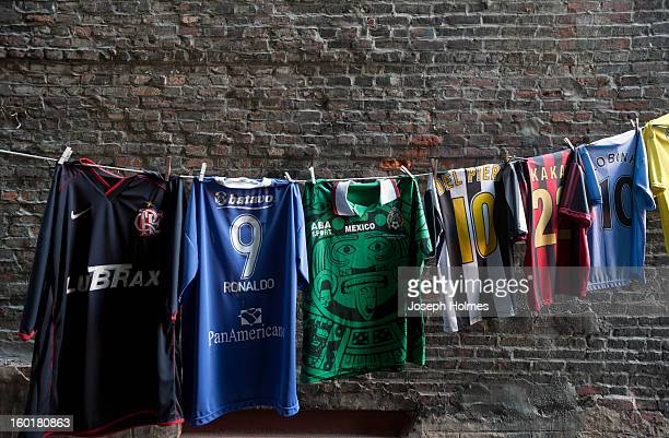 Soccer shirts representing teams from around the world hang on a clothes line against a brick wall in New York City.
