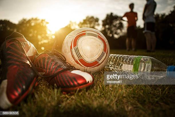 Soccer shoes, ball and bottleof water on soccer pitch