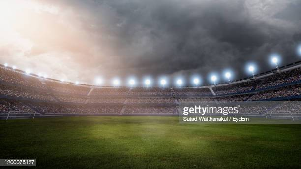 soccer stadium against sky at dusk - football ストックフォトと画像