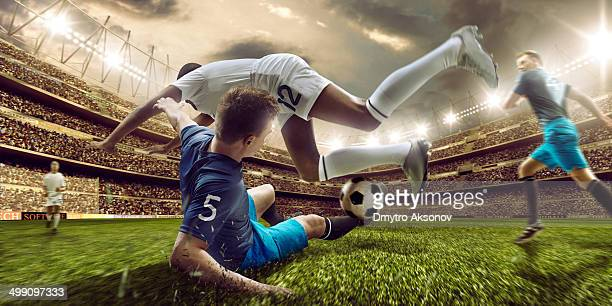 soccer stadium and soccer players in action - tackling stock pictures, royalty-free photos & images