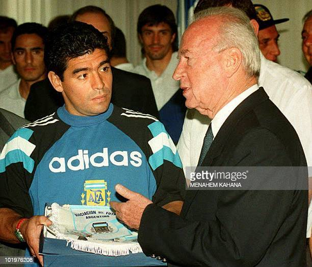 Soccer star Diego Maradona gives the Argentinian team's pennant to Israeli Prime Minister Yitzhak Rabin in Jerusalem Israel 30 May 1994
