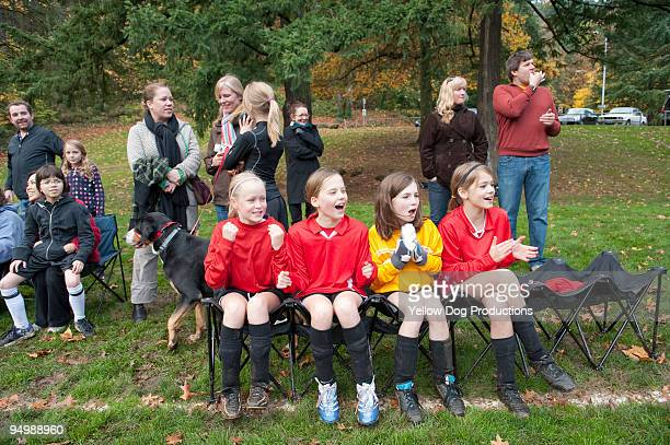 Soccer team and spectators cheering on sidelines