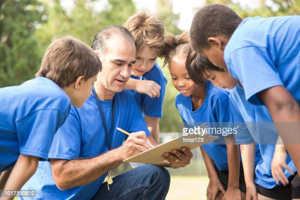 Soccer team coach explains next play to his children's team.