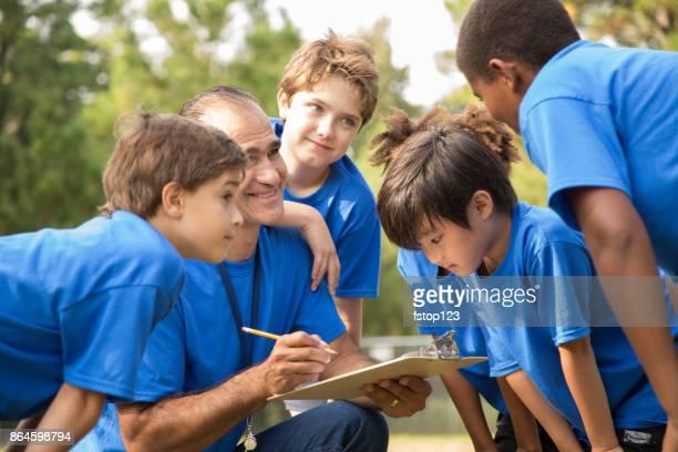 voetbal team coach legt volgende spelen van zijn kinderen team. - jeugdsportcompetitie stockfoto's en -beelden