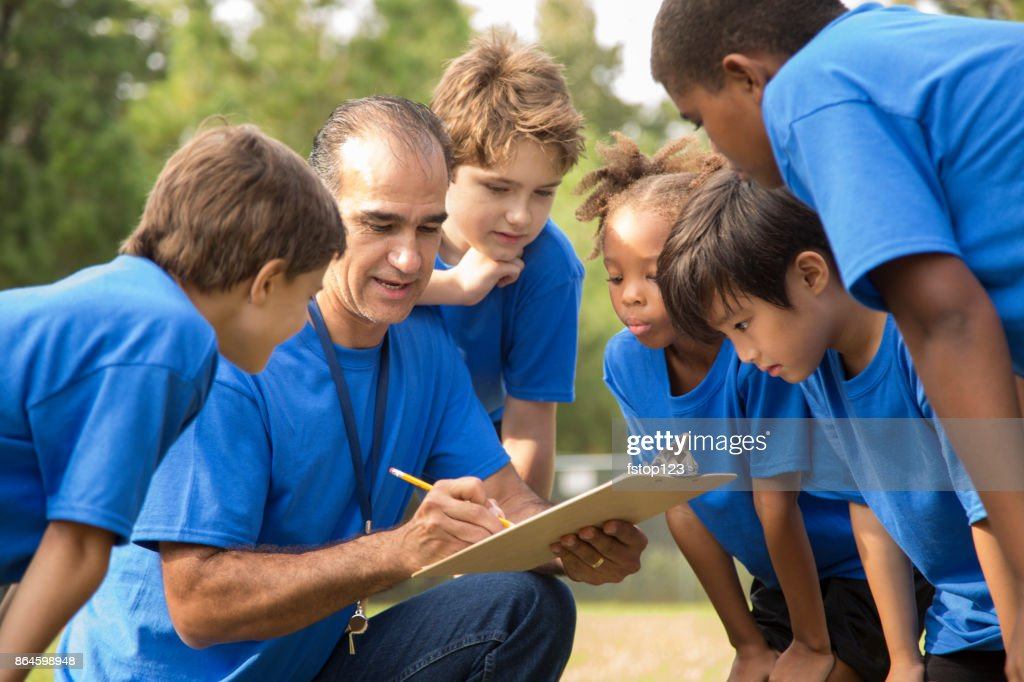 Soccer team coach explains next play to his children's team. : Stock Photo