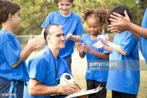 soccer team coach explains next play to his children's team. - football team stock pictures, royalty-free photos & images