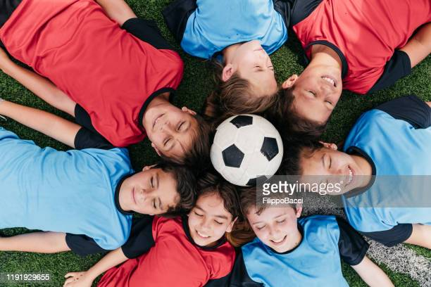 soccer team kids lying down in circle with a soccer ball in the center - fair play sport foto e immagini stock