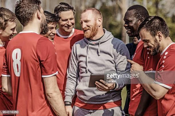 eine fußballmannschaft, die taktik auf einem tablet während einer fußball-trainingseinheit mit dem trainerteam betrachten - trainer stock-fotos und bilder