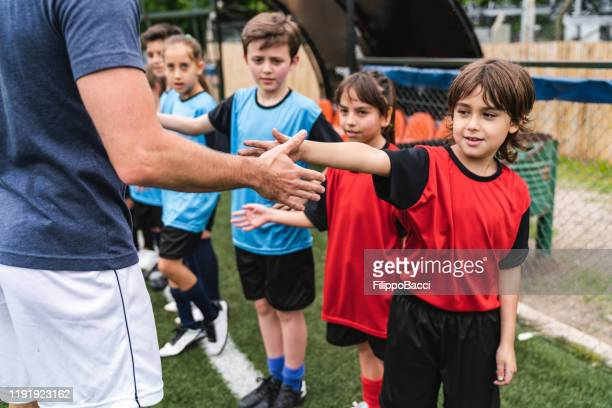 soccer team of kids high five their coach - junior level stock pictures, royalty-free photos & images