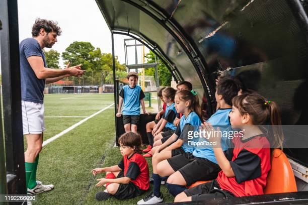 fußball-team von kindern sitzen auf einer bank und hören ihrem trainer - jugendmannschaft stock-fotos und bilder