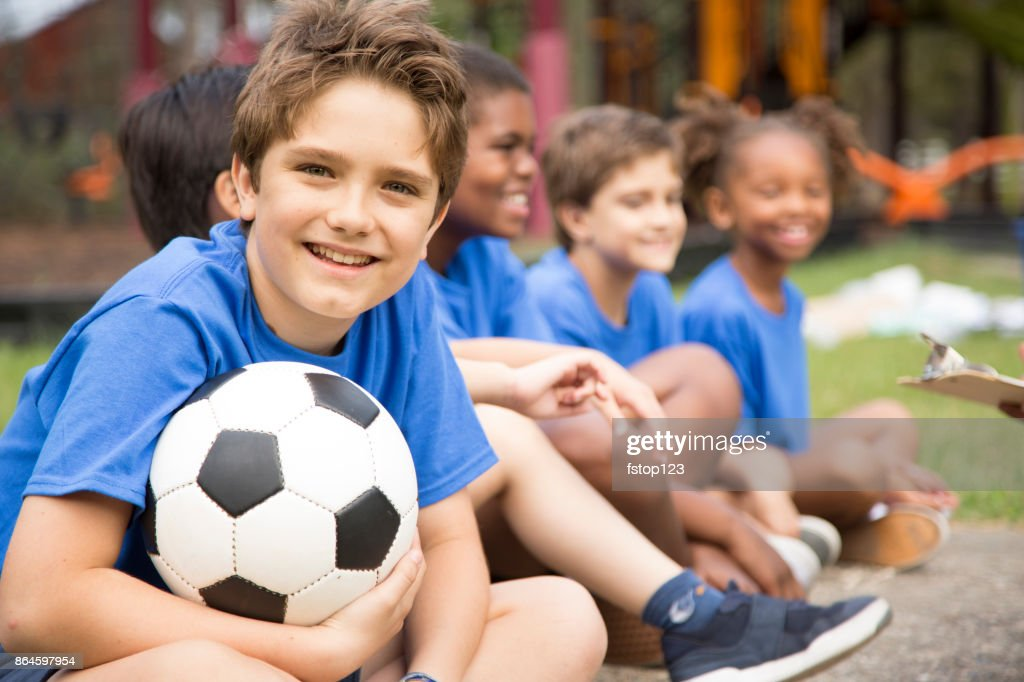 Soccer team players sit and listen to coach explain next play. : Stock Photo