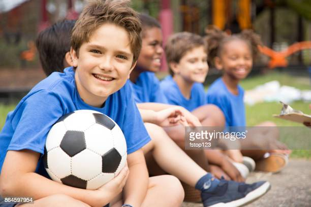 soccer team players sit and listen to coach explain next play. - sports team event stock photos and pictures
