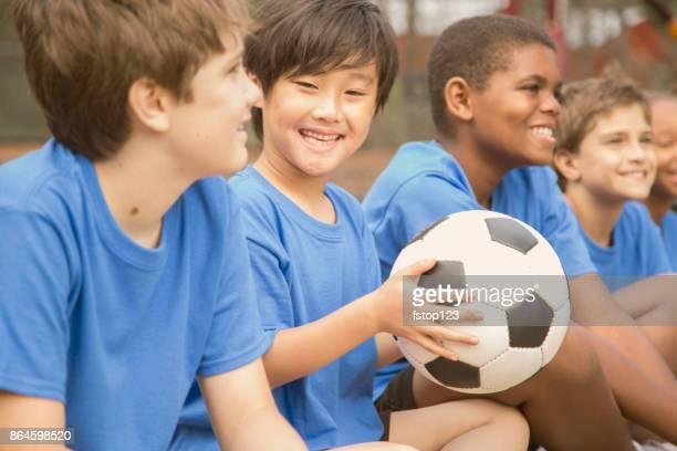 voetbal team spelers zitten en luisteren naar coach verklaren volgende spelen. - jeugdsportcompetitie stockfoto's en -beelden