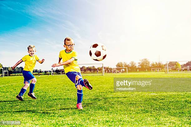 soccer team plays game and boy kicks ball - kicking stock pictures, royalty-free photos & images