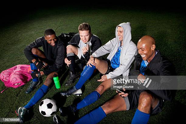 サッカーチームの試合観戦の後の休息にピッチ - 若い男性だけ ストックフォトと画像