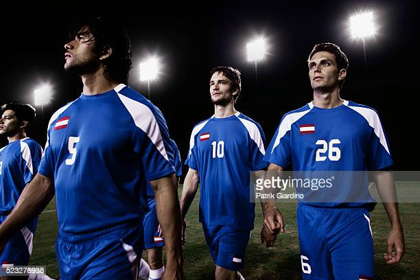 soccer team walking on the field - football team stock pictures, royalty-free photos & images