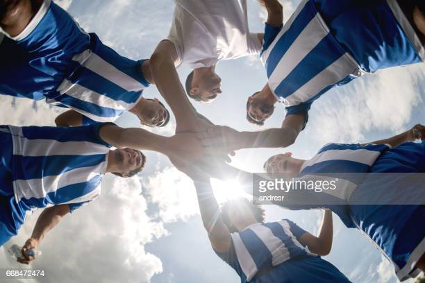 soccer team with hands together on the field - squadra sportiva foto e immagini stock