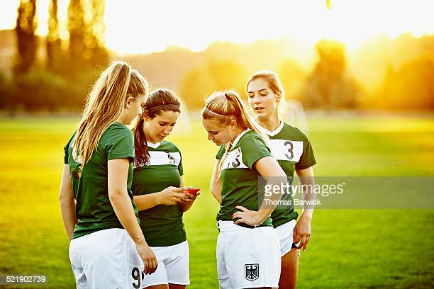 Soccer teammates looking at messages on smartphone
