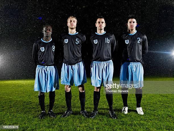 Soccer teammates standing on field in rainstorm