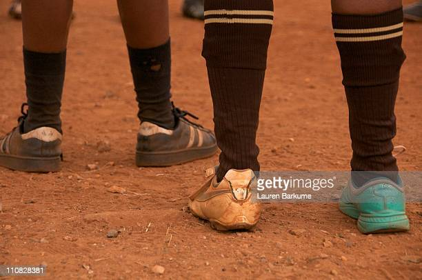 Soccer Team's Mismatched Shoes on Dirt Field