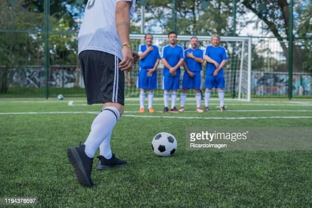 voetbalteams van latijnse gentlemen play soccer match en een team laadt een vrije trap - verdediger voetballer stockfoto's en -beelden