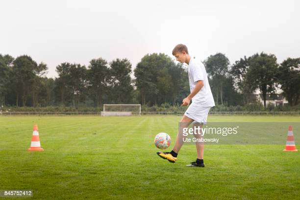 Soccer training on a sports ground A boy practices dribbling with a football Staged picture on August 10 2017 in Duelmen Germany