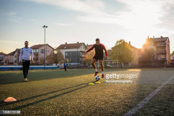 fußballtraining mit zukunftsaussichten - fußballstürmer stock-fotos und bilder