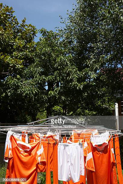 Soccer uniforms hanging from clothesline outdoors