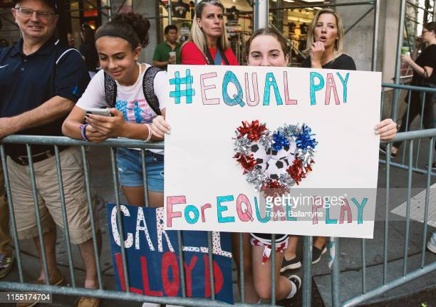USWNT Women's World Cup Parade Young fan holding up sign that reads EQUAL PAY FOR EQUAL PAY while watching parade going through Canyon of Heroes...