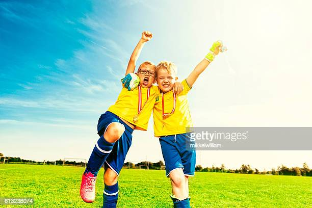 Soccer victory celebration with two football kids cheering