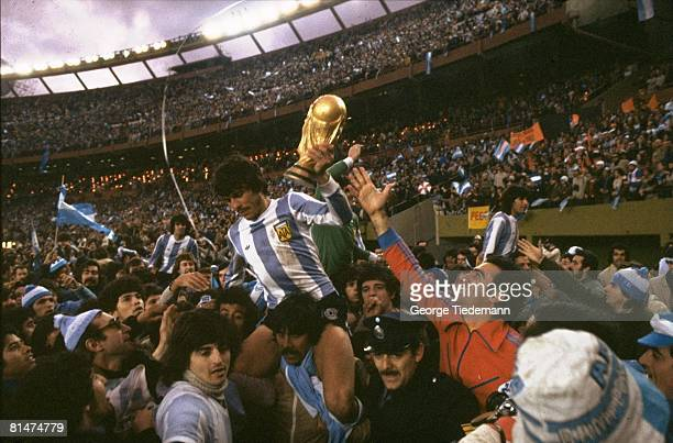 Soccer World Cup Final Argentina Daniel Passarella victorious with trophy getting carried off field by teammates after winning game vs Netherlands...