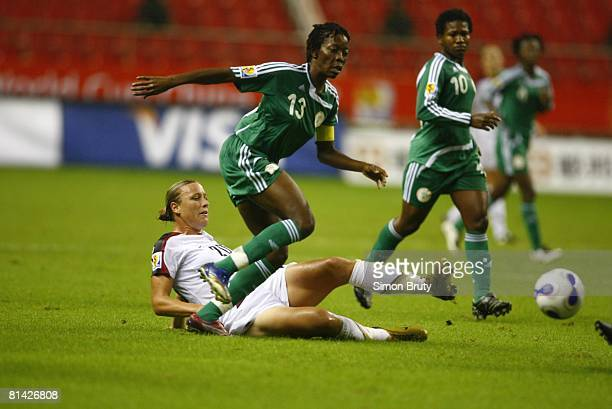 Soccer World Cup USA Abby Wambach in action slide tackle vs Nigeria Christie George Rain weather Shanghai China 9/18/2007