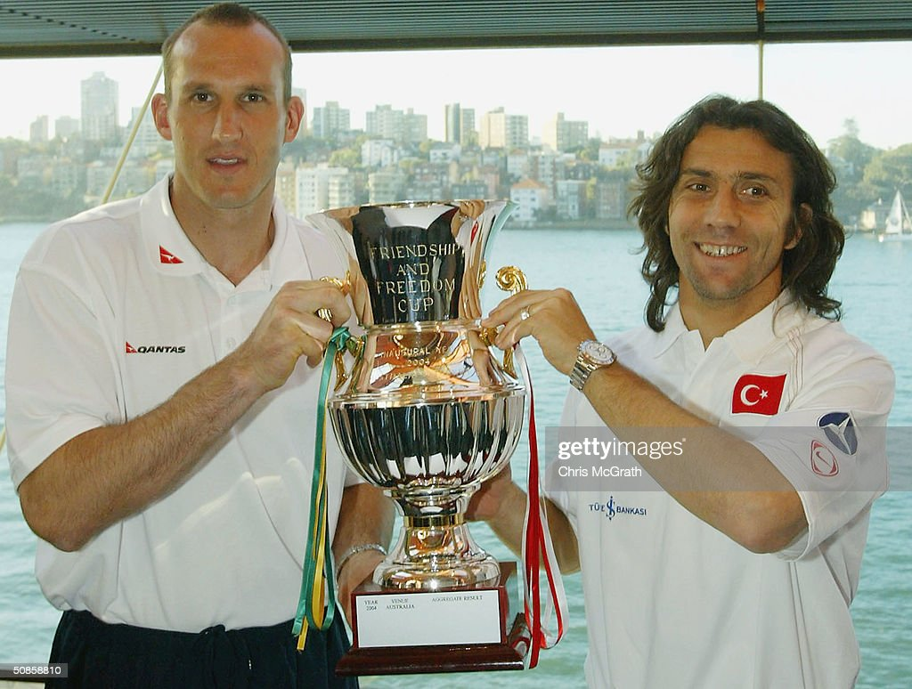 Socceroos Captain Mark Schwarzer and Turkey captain Bulent Korkman pose for photos with the Friendship and Freedom cup during the official welcoming ceremony for the Turkish soccer team held at the Sydney Opera House, May 20, 2004 in Sydney Australia.