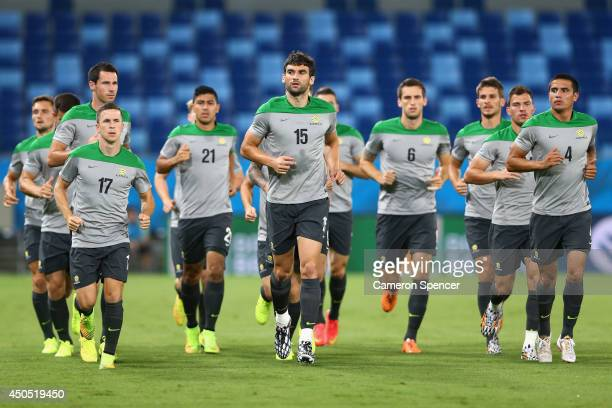 Socceroos captain Mile Jedinak and team mates warm up during an Australian Socceroos training session at Arena Pantanal on June 12, 2014 in Cuiaba,...