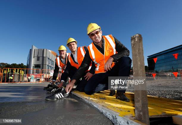 Socceroos Coach Graham Arnold, Former Rugby Union player Phil Waugh and Former Rugby League player Brad Fittler pose as they lay the prints of their...
