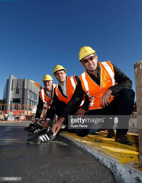Socceroos Coach Graham Arnold Former Rugby Union player Phil Waugh and Former Rugby League player Brad Fittler pose as they lay the prints of their...