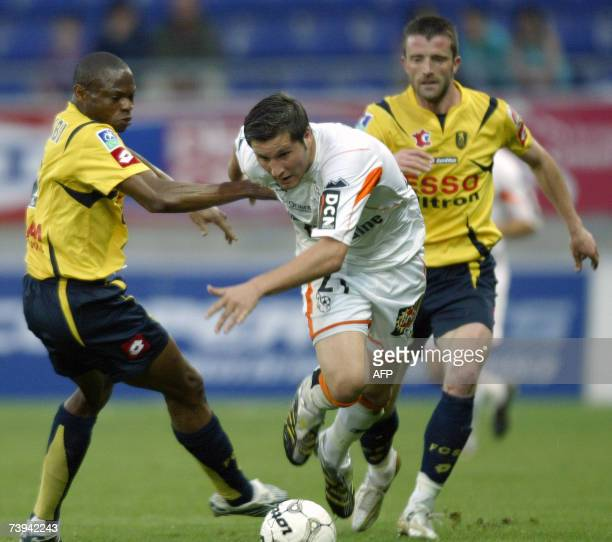 Sochaux' Nigerian defenders Rabiu Afolabi and French defender Stephane Pichot vies with Lorient's French forward AndrePierre Gignac during their...