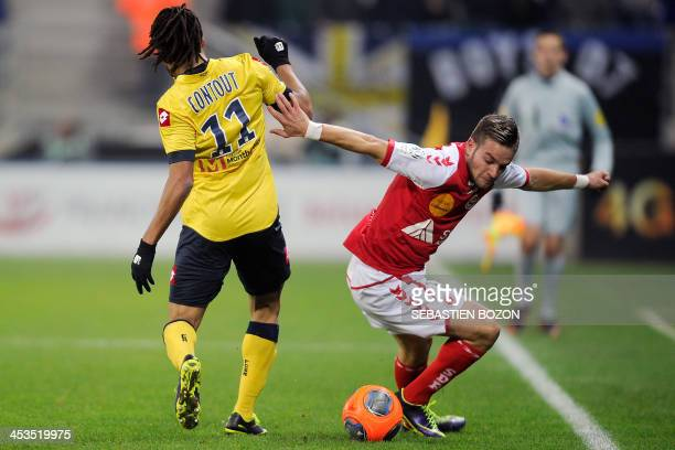 Sochaux's French forward Roy Contout challenges Reims' French defender Atila Turan during the French L1 football match between Sochaux and Reims at...