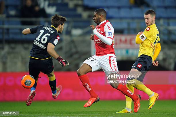 Sochaux's French goalkeeper Simon Pouplin fails to stop the ball as Reims' French defender Christopher Glombard advances past Sochaux's French...