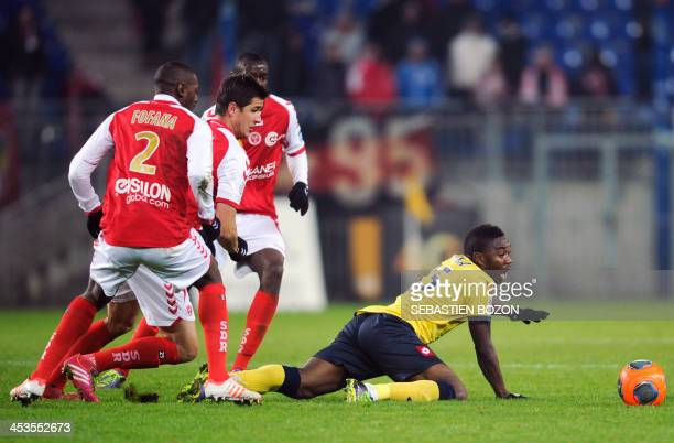 Sochaux's Zambian forward Emmanuel Mayuka falls after challenging Reims' Malian defender Mohamed Fofana, French defender Anthony Weber and Congolese...