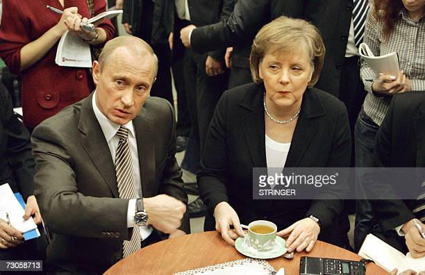 Sochi, RUSSIAN FEDERATION: Russian President Vladimir Putin and Germany?s Federal Chancellor Angela Merkel have a cup of tea as they are surrounded...