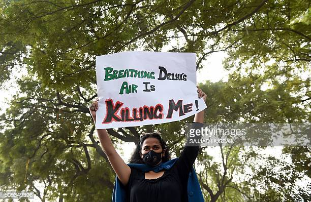 A social activist holds a placard during an awareness rally against air pollution under the banner 'Help Delhi Breathe' in New Delhi on January 17...